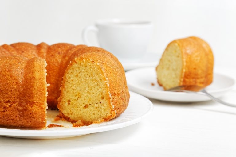 Homemade round lemon cake soaked with lemon syrup on white wooden table. Cutted off piece and cup of tea on blurred background. Shallow focus.